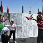 Israeliska soldater hjälper demonstranter att riva mur